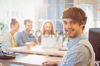 Portrait of smiling young businessman with colleagues