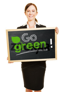 Geschäftsfrau hält Tafel mit Go Green