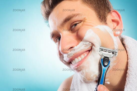 Happy man shaving using razor with cream foam.