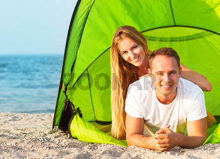 Happy young couple camping on the beach