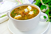 Soup lentil with spinach and feta in white cup on board