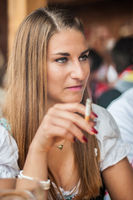 Young woman in Dirndl dress sitting and smoking at the Oktoberfest