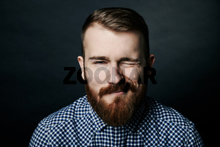 Winking red bearded man studio portrait on dark background