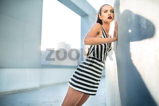Fashion model in a striped dress near the wall