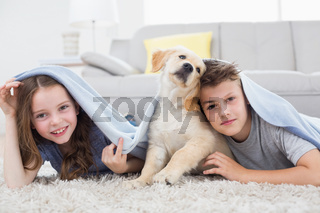 Cute siblings with dog under blanket in living room