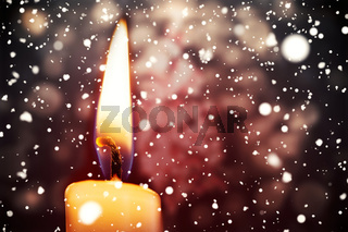 Snow falling against candle burning