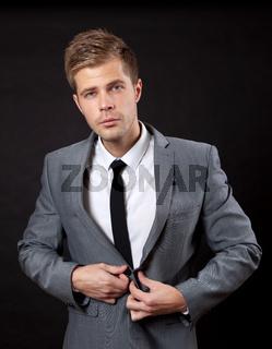 Confident young businessman buttoning suit
