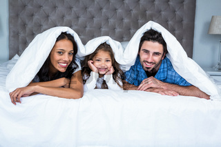 Happy family under the blanket