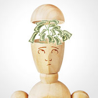 Money tree grows into the human head. Abstract image with a wooden puppet