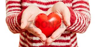 Hände halten rotes Herz als Symbol