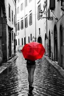 Woman with red umbrella on retro street in the old town. Wind and rain