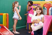 Mädchen mit Plüschtier im Kindergarten