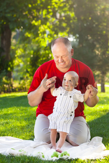 Happy father and his son playing in park together. Outdoor portrait of happy family