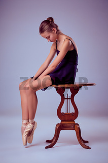 young ballerina sitting on wooden chair