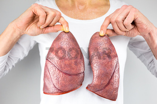 Woman holding two lung models in front of chest