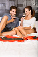 A young couple with a glass of wine in an asian style hotel room