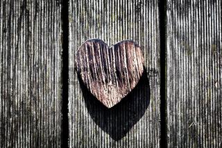 A wooden vintage heart on grunge wood planks. Symbol of love