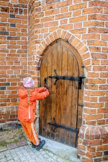 Little beautiful girl opens door in fortress