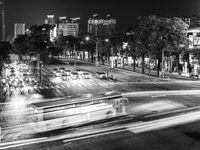 Cars, buses, motorcycles on road at night in black and white, Taichung, Taiwan, Asia.