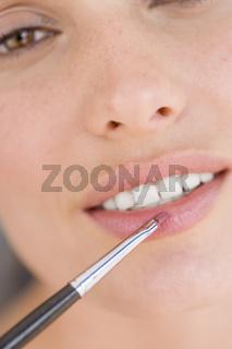 Beauty Portrait junge Frau traegt Lippenstift mit Pinsel auf, Nahaufnahme