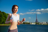 Redhead sexy girl running at sunset in the summer against the backdrop of the Eiffel Tower.