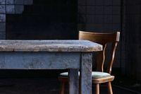 Wooden table and chair in a tiled room