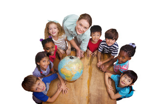 Composite image of cute pupils smiling around a globe in classroom with teacher