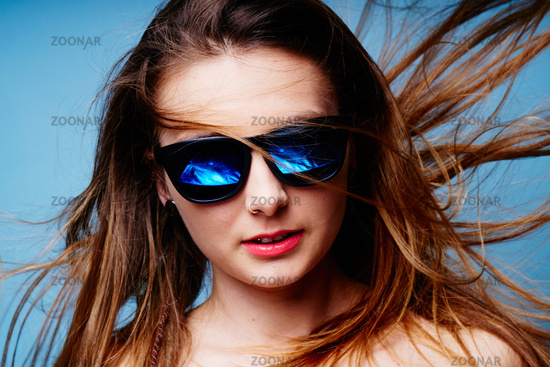 Young female with sunglasses, her hair flying