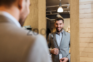 man trying jacket on at mirror in clothing store