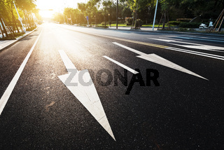sunlight and empty asphalt road with traffic sign