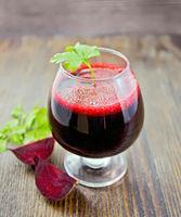 Juice beet in wineglass on board