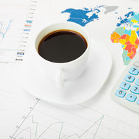 Coffee cup and calculator over world map and some financial charts