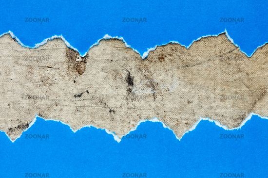 Torn blue paper on dirty canvas