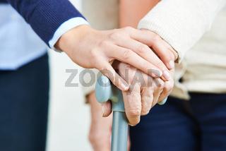 Frau hält Hand mit einer Seniorin