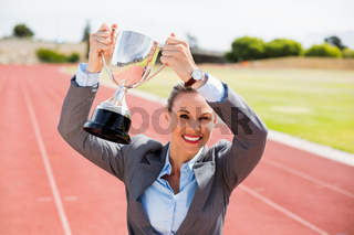 Portrait of happy businesswoman holding up a trophy