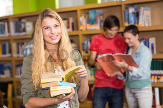 Female college student holding books in library