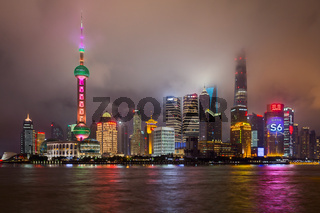 Skyline of Shanghai in clouds by night