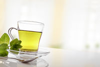 Cup of green tea with mint front diagonal view