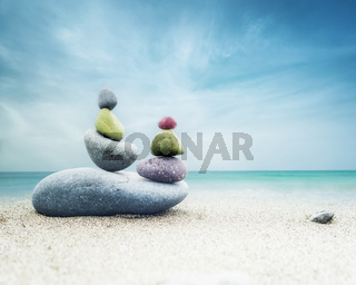 Balancing colorful zen stones pyramid on sandy beach under blue sky