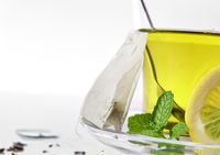 Green tea with mint and lemon with teabag closeup