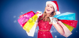 Composite image of excited blonde in santa hat holding shopping bags