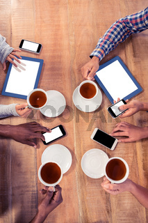 Business colleagues using technologies at desk while holding coffee cups