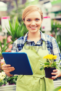 happy woman with tablet pc in greenhouse