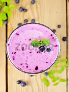 Milkshake with blueberries on board top