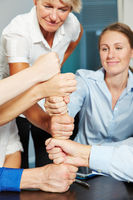 Business Team baut Turm aus Fäusten