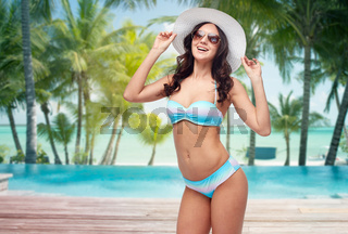 happy young woman in bikini swimsuit and sun hat