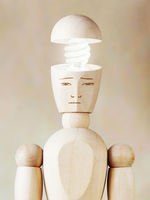 Glowing light bulb in the human head. Concept of genius. Abstract image with wooden puppet