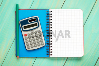 Calculator,pencil and open notebook.