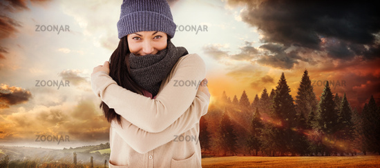 Composite image of attractive brunette looking at camera wearing warm clothes