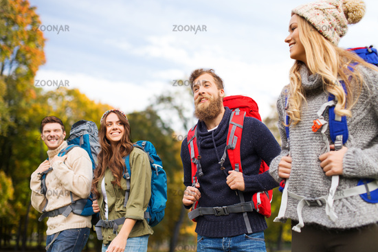 smiling friends with backpacks hiking over nature